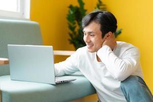 asiatisk man som sitter på golvet som gör ett videosamtal foto