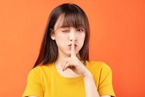 bild av ung asiatisk kvinna som bär gul t-shirt på orange bakgrund foto