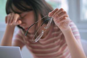 ung asiatisk tjej trött på att arbeta länge på datorn foto