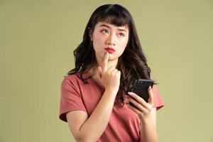 den asiatiska kvinnan höll telefonen med ett tankeväckande uttryck foto
