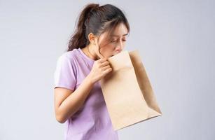 ung asiatisk tjej munkavle i en papperspåse foto