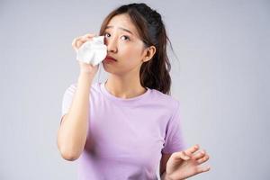 ung asiatisk kvinna torkar tårarna med en vävnad foto