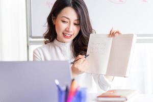 asiatisk kvinnlig lärare som undervisar online hemma foto