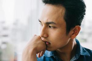 ledsen asiatisk man vid fönstret foto