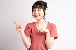 ung asiatisk kvinna som poserar på vit bakgrund, använder fingret för att peka och visa, handgest foto