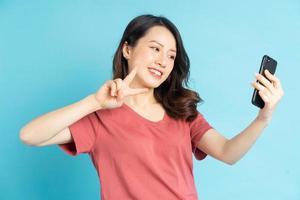 asiatisk kvinna använder smartphone för att ta selfies foto