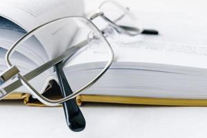 öppen bok och glasögon, närbild foto