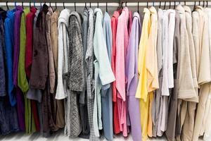 olika färgade badrockar på galgen i duschrummet foto