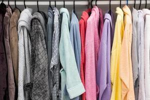badrockar i olika färger på galgen i duschrummet foto