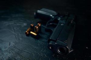 svart pistol och kulor på bordet. foto