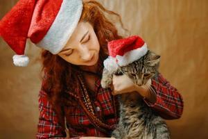 kvinna i jultomtenhatt med katt i julhatt. foto