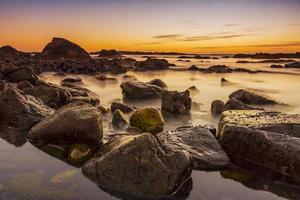 stenig strand med gyllene färger vid solnedgången foto