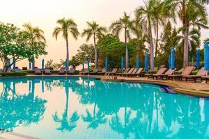 solstolar eller poolbäddar med parasoller runt poolen vid solnedgången foto
