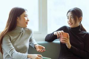 asiatiska kvinnor som chattar vid fönstret foto