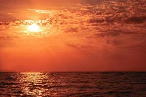 varm sommarsolnedgång över havet i röda färger foto