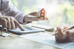 fastighetsmäklare som diskuterar om lån och räntor för att köpa hus till kunder som kommer i kontakt. kontrakt och avtalskoncept. foto