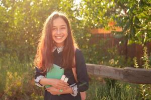 ganska ung flicka med en ryggsäck och anteckningsblock. skolflicka tonåring flicka leende med anteckningsblock. foto