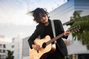porträtt man håller gitarr spelar musikfestival utomhus, livsstil mode musikgata utomhus foto