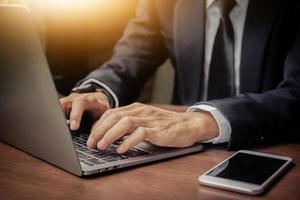 närbild hand med dator, affärsman skriver laptop foto