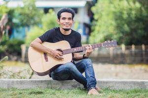 man spelar gitarr utomhus glad på sommaren foto