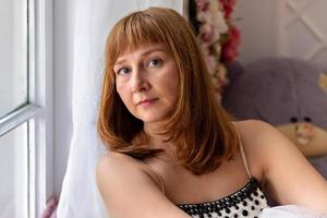 porträtt av en vacker ung kvinna som sitter vid fönstret. närbild foto