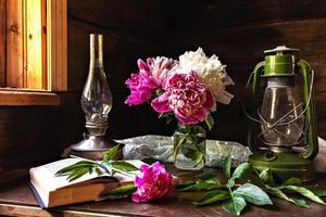 stilleben av vintageartiklar och en bukett pioner på ett bord vid fönstret i ett gammalt byhus. foto