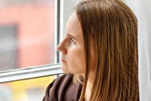 porträtt av en ung fundersam kvinna som sitter vid fönstret. närbild foto