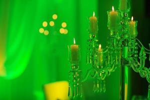 bröllop dekoration. kristallkandelaber med ljus i grönt ljus foto
