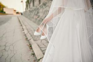 bruden i bröllopsklänning och slöja går ner på gatan med skor i handen foto