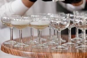 mousserande vin, champagne i glas på träbordet. servitören i svarta handskar häller alkohol i glasen i restaurangen. selektivt fokus foto