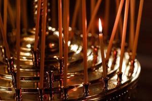 många ljus som brinner på natten i kyrkan. grupp av brinnande ljus i mörkret. närbild. kopiera utrymme. foto