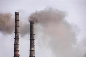 rök från två industriella skorstenar, rör, mot himlen. Global uppvärmning. luftförorening. ekologisk förorening. luftutsläpp som förorenar staden. industriavfall är hälsofarligt. foto