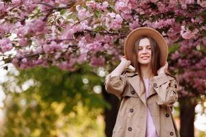 porträtt av ung vacker fashionabla flicka i hatt poserar nära blommande träd med rosa blommor på en solig dag foto