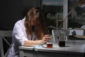 kvinnlig läkare som sitter vid bordet och håller glas med whisky eller cognac hemma efter hårt arbete, deprimerad kvinna som dricker stark alkohol som lider av koronavirusproblem. foto