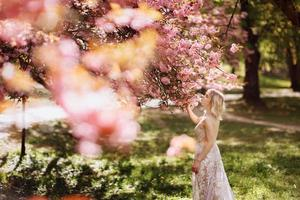vacker flicka har doften av blommande träd. porträtt av vacker kvinna med blommande körsbärsträd - flicka andas in doften av blommor med slutna ögon - vår-, natur- och skönhetskoncept foto