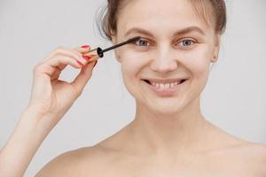 vacker brunett kvinna målar ögonfransarna. vacker kvinna ansikte. sminkdetalj. skönhet flicka med perfekt hud foto