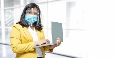 affär asiatisk dam som bär bärbar dator för ansiktsmask i office med kopieringsutrymme. foto