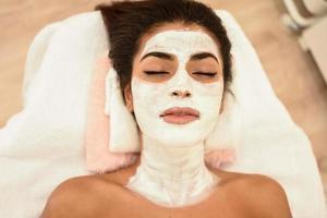 ung kvinna med fuktkrämkrämmask på hennes ansikte foto