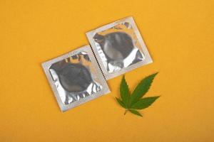 kondomer och marijuanablad på gul bakgrund, kön och droger, preventivmedel efter droganvändning foto