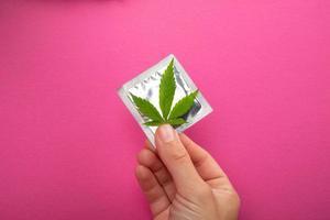 skydd vid sex när man använder droger, kondom och cannabisblad på rosa bakgrund foto