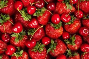 färsk bakgrund, nyplockade jordgubbar och körsbär, bakgrund med säsongens bär och frukter foto