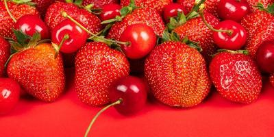 söta körsbär och jordgubbar på ett rött bakgrundsslut upp foto