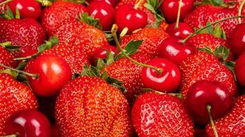 söta körsbär och jordgubbar på en röd bakgrundscloseup foto