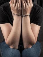 kvinna i handbojor täckte ansiktet och beklagar brottet foto