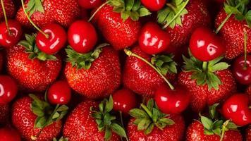 jordgubbar och söta körsbär nära uppred bakgrund foto