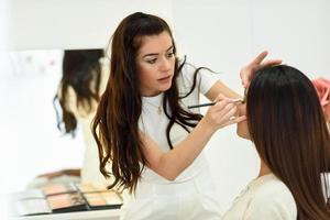 make-up artist sätter ögonskugga på en afrikansk kvinna. i ett skönhetscenter. foto