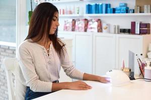 kvinna som använder manikyrerade naglar i uv-lampa. foto
