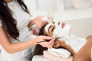 estetik applicerar en mask på en vacker kvinnas ansikte foto