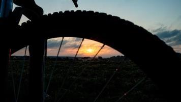 cykelturism kvällssolnedgång, orange sol på en silhuett cykel hjul bakgrund foto