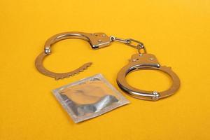 handbojor och kondomer på gul bakgrund, olaglig sexprostitution foto